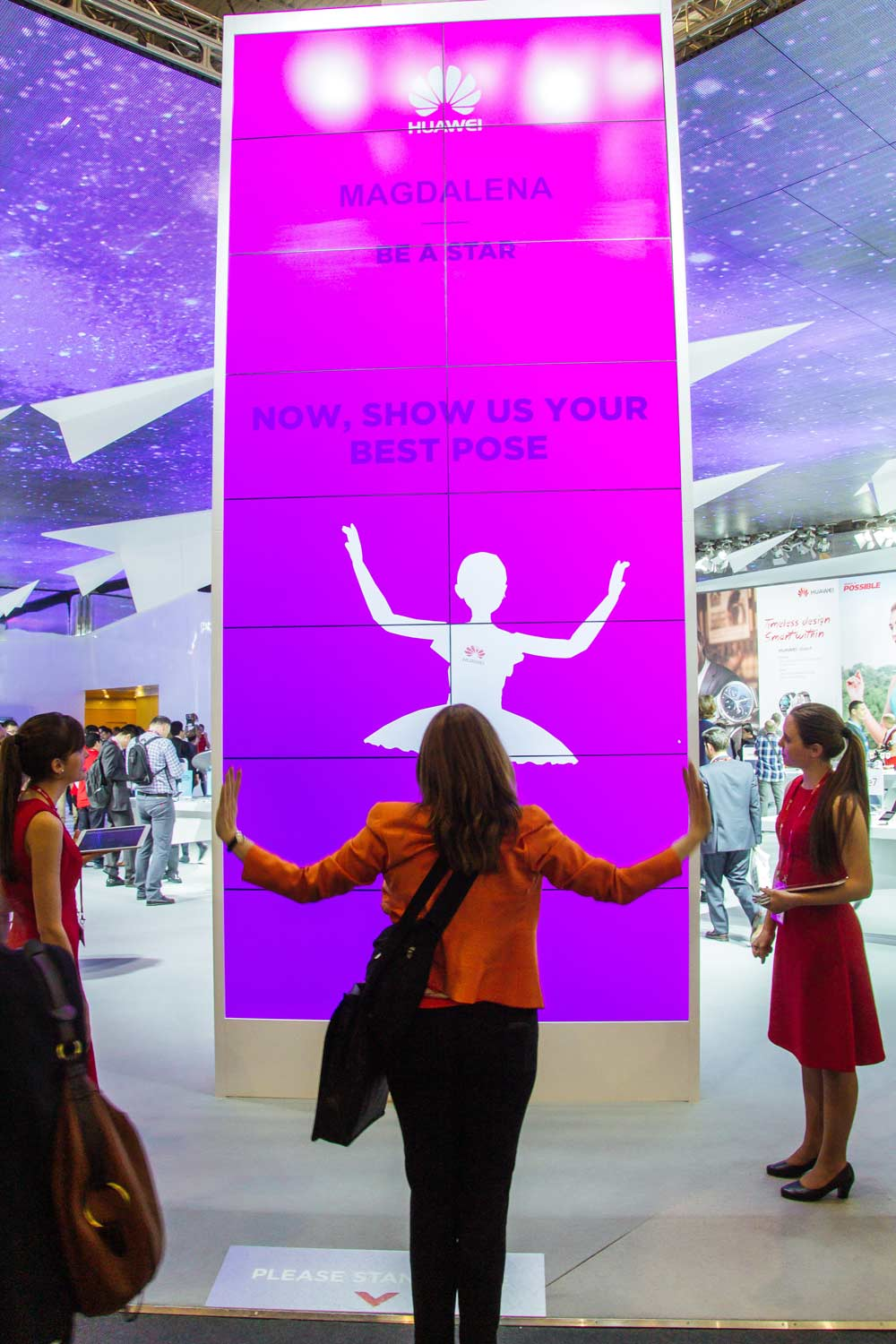 women pretend to be a ballerina in front of interactive wall