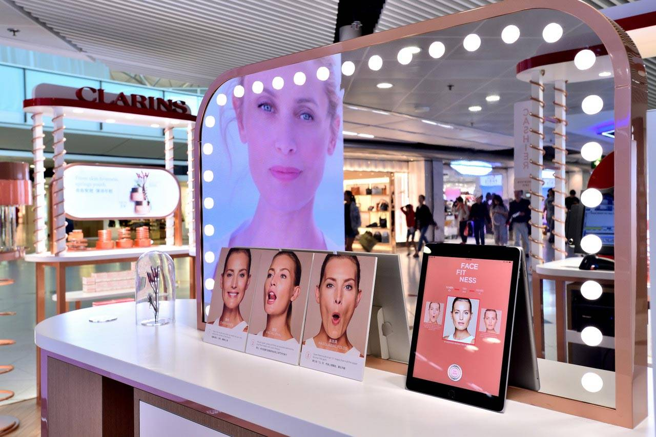 Clarins shop with mirror and image showing women faces